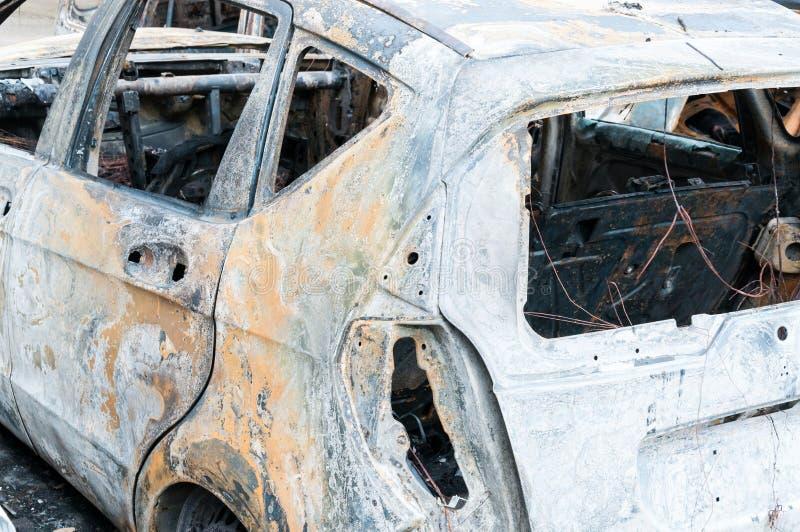 Totalt förstörda bilar brände i brand i krigzonen eller i nära övre för borgerliga demonstrationer arkivfoton