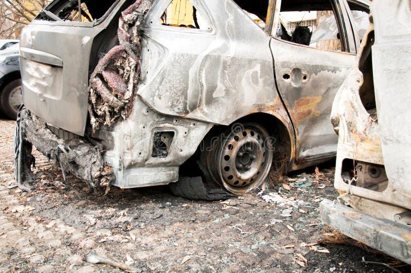 Totalt förstörda bilar brände i brand i krigzonen eller i nära övre för borgerliga demonstrationer royaltyfri bild