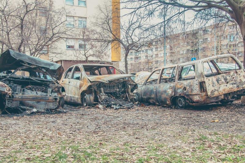 Totalt förstörda och skadade bilar brände i brand i krigzonen eller i nära övre för borgerliga demonstrationer royaltyfri fotografi