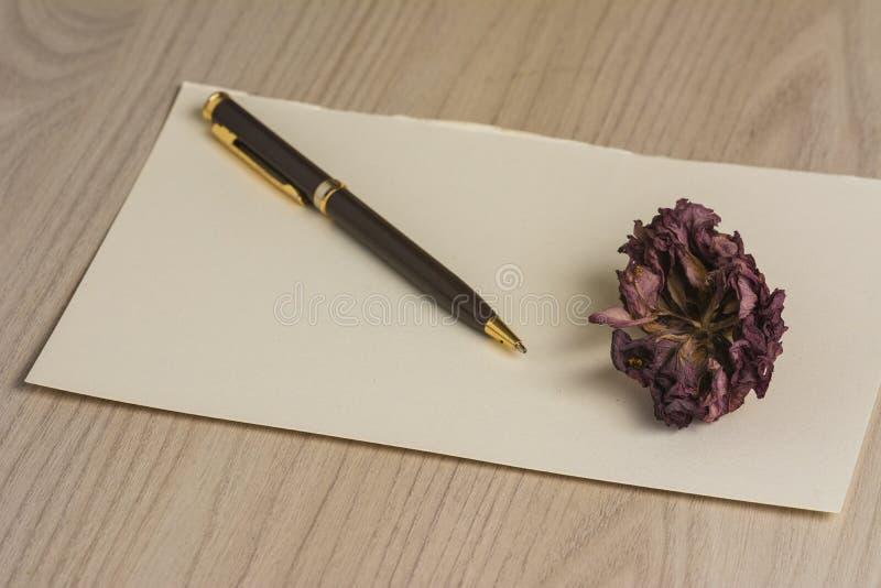 Tote Blume auf einem Buchstaben lizenzfreie stockfotografie