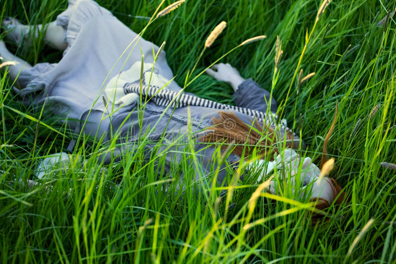 Tote Frau, die in Gras legt lizenzfreies stockbild