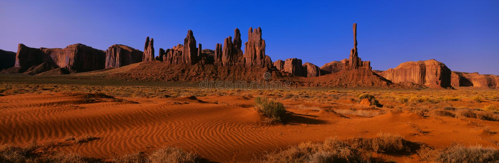 The Totem Pole. This is Yei Bi Chei and The Totem Pole at sunrise. In front are the sand dunes of Monument Valley royalty free stock photos