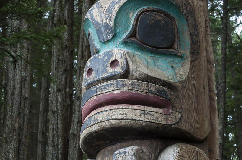 Totem pole. Closeup of face of wooden Tlingit totem pole in dense pine forest in Sitka, Alaska royalty free stock photography