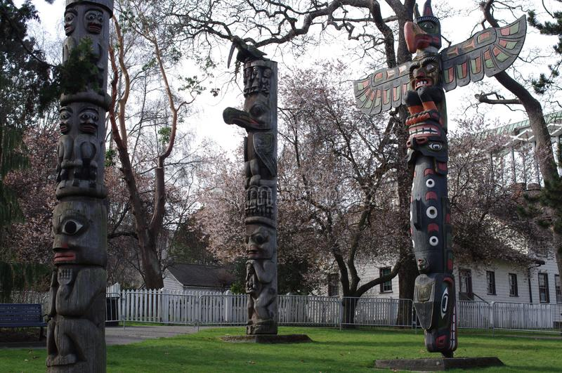 Totem poles among early spring blooming trees royalty free stock photo