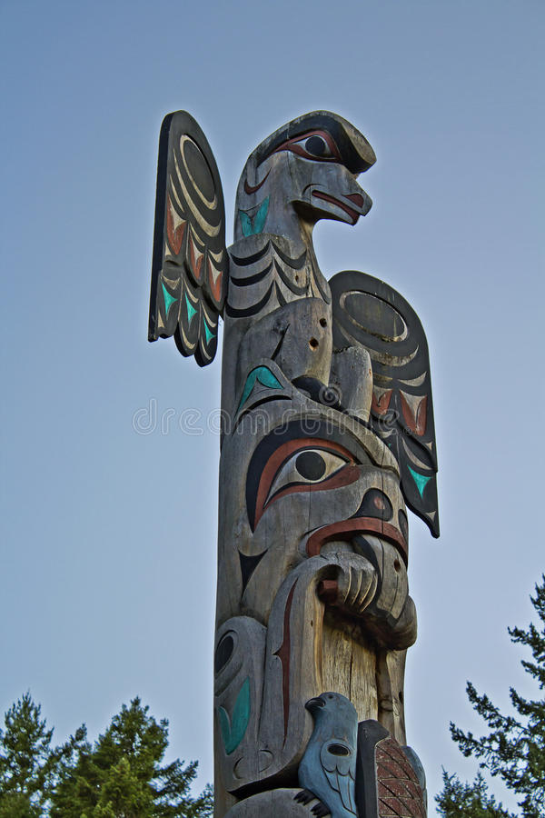 Totem. Poles are monumental sculptures carved on poles, posts, or pillars with symbols or figures made from large trees, by indigenous peoples of the Pacific stock images