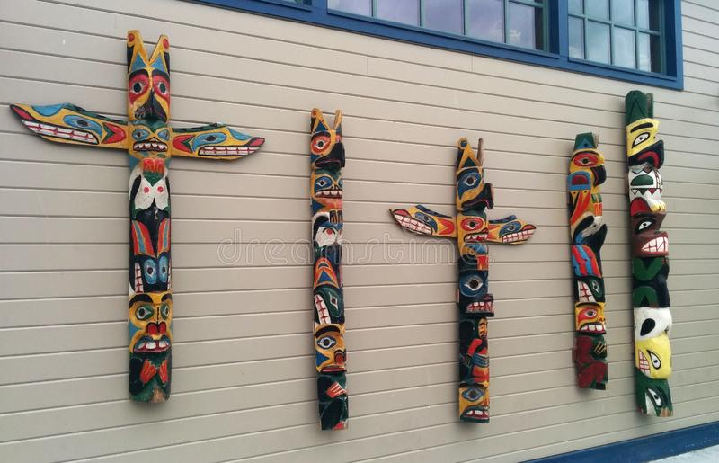 Totem poles on a wall outside Ye Olde Curiosity Shop stock image