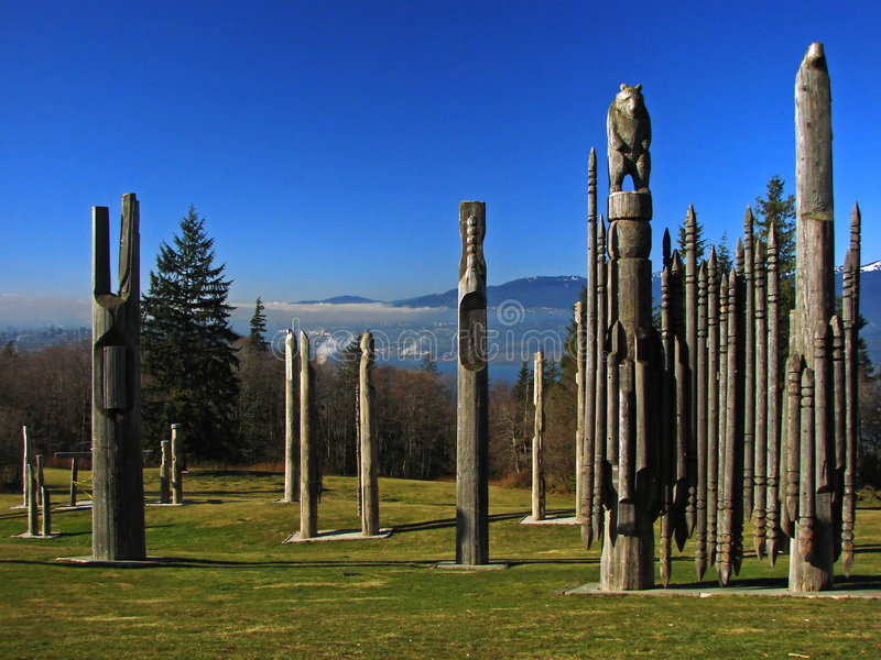Totems in Vancouver, BC, Canada. Totem poles on top of Burnaby Mountain in the Vancouver area, BC, Canada. There was a layer of fog hanging above the city royalty free stock image