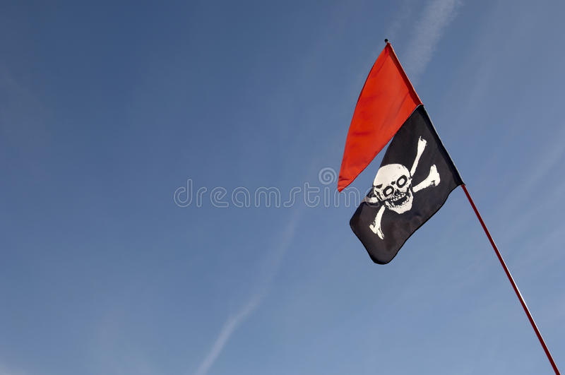 Totenkopf mit gekreuzter Knochen-Flagge stockbild