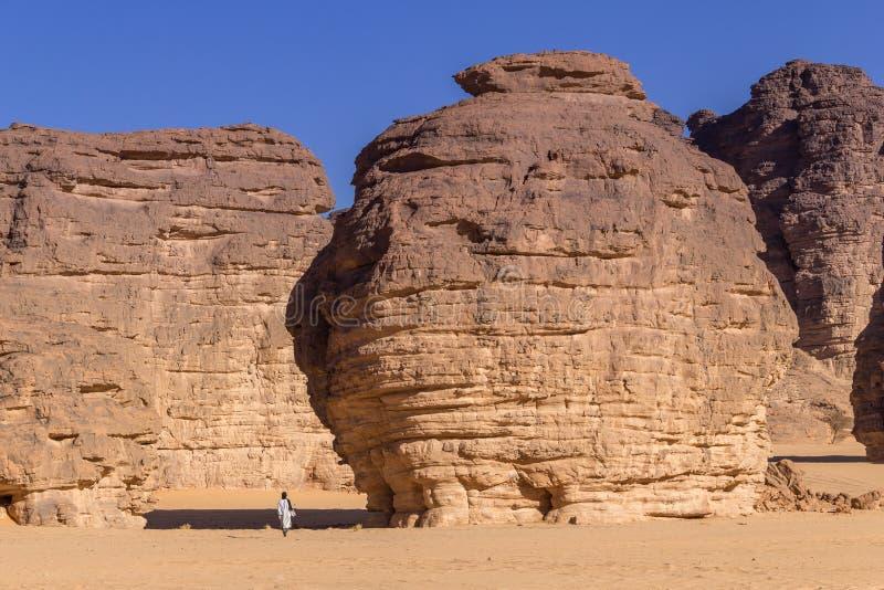 Touareg, das zwischen enorme Felsen in der Sahara-Wüste von Algerien geht stockfotografie