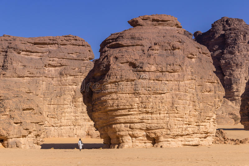Touareg die tussen massieve rotsen in de woestijn van de Sahara van Algerije lopen stock fotografie