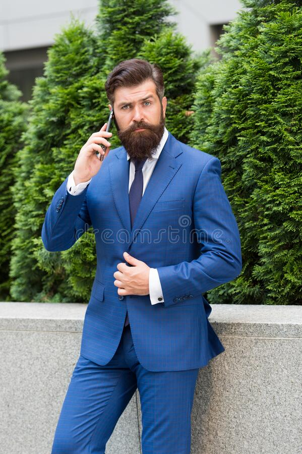 In touch with clients. ceo walk in street. boss man speak on phone. Businessman make business call. energy efficiency. Concept. bearded man in jacket near royalty free stock images