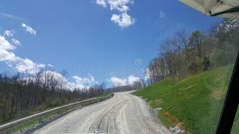 Touch clouds on mountain. Lease roads, gravel, lease road, work, summer, blue sky, puffy clouds, guardrail, trees, wildand wonderful, West Virginia, peterbilt stock image