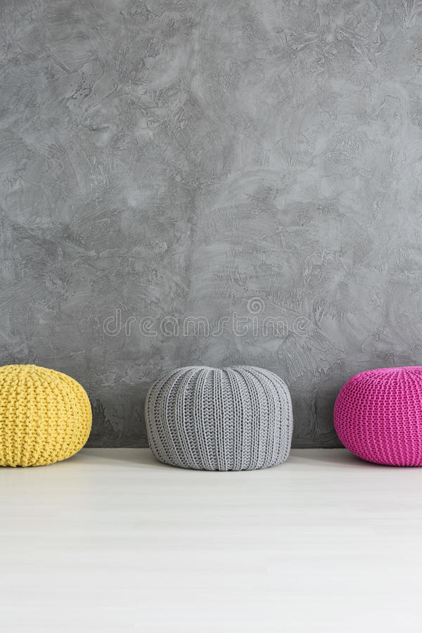Touch of color in a grey interior. Three color poufs standing beside grey wall with decorative finish stock images