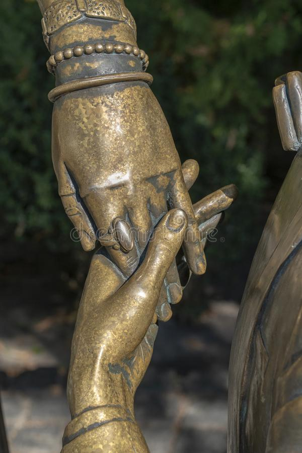 Touch of female and male hands. Detail of a bronze sculpture. Close up royalty free stock photo