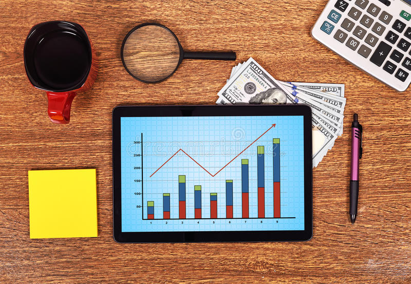 Touch pad with stock chart. On yellow table stock photography
