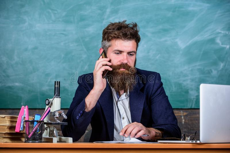 In touch with school. School principal or teacher calling parents to report about exam results. Man with beard talk. Phone classroom background. School teacher stock photography