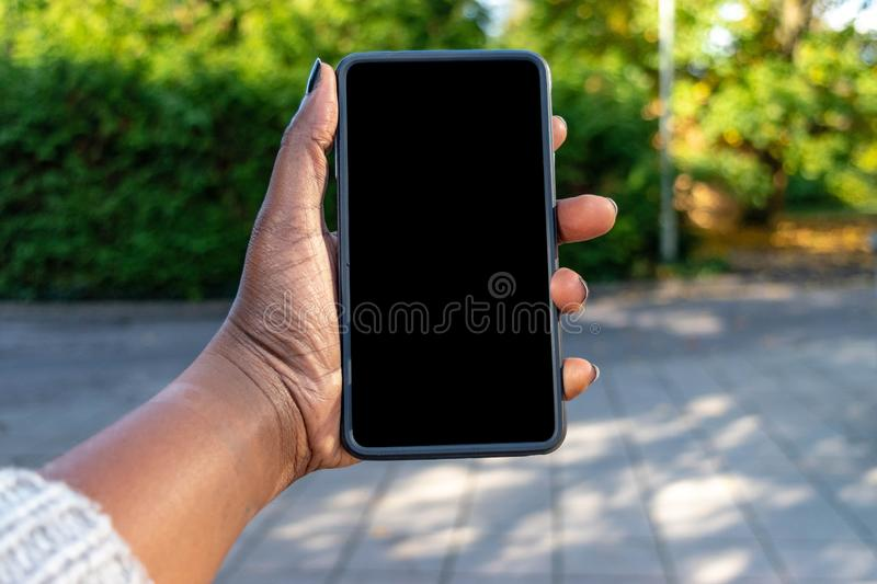Touch screen mobile phone, in African woman`s hand. Black Female holding smart phone on green outdoor background with blank copy s royalty free stock photography