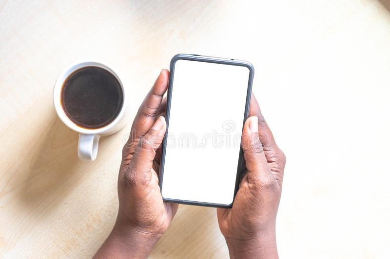 Touch screen mobile phone, in African woman`s hand. Black Female holding smart phone on green outdoor background with blank copy s stock photo