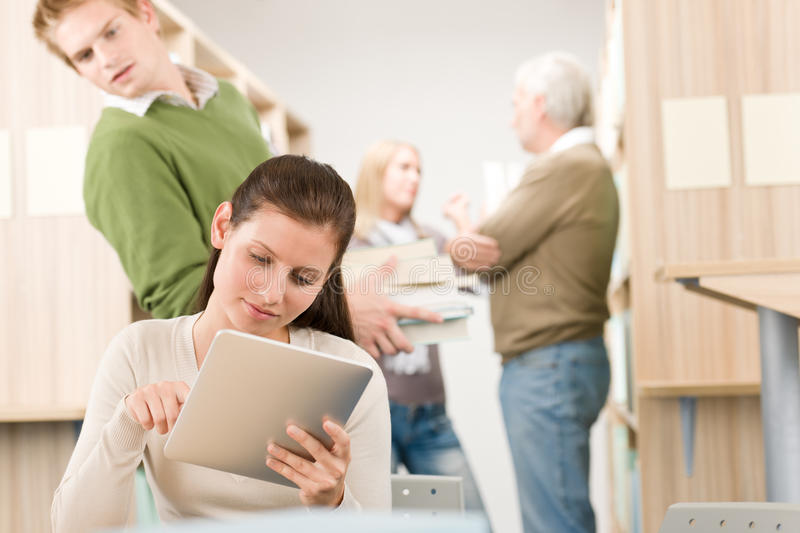 Touch screen tablet computer - students in library. Touch screen tablet computer - group of students in library royalty free stock images