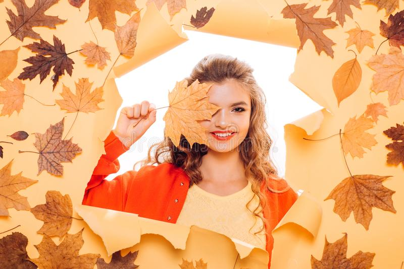 Touches of gold leaf. Young woman look out of hole. Makeup girl peek through torn paper. Pretty girl cover face with. Autumn leaf. Fashion model with decorative royalty free stock images