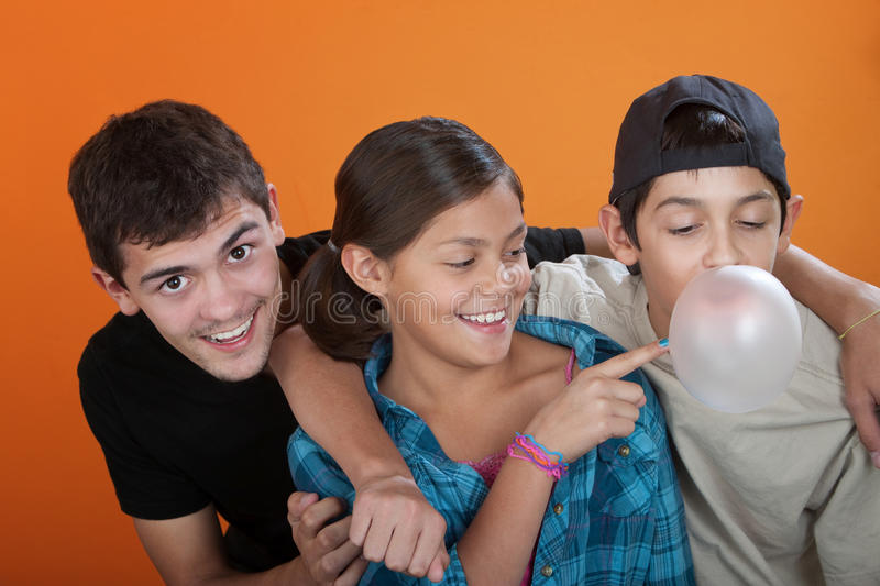 Touching a bubble from her brothers gum. Young girl touching bubble from her brothers chewing gum on orange background stock photo