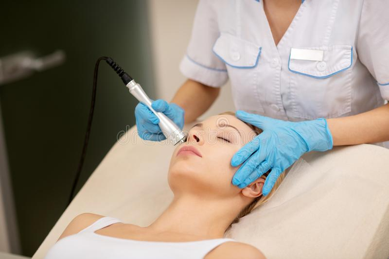 Dermatologist touching face of client while doing skin tightening royalty free stock photos