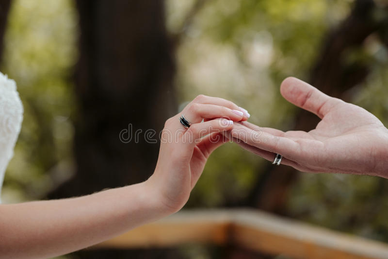 Touching the fingers of the bride and groom. Light, gentle, sensual and slightly mysterious. On their hands are engagement rings. Space for text stock photos