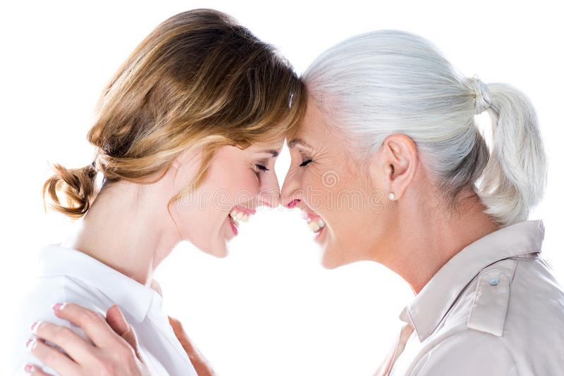Touching foreheads. Happy senior mother and adult daughter touching foreheads, isolated on white stock photos