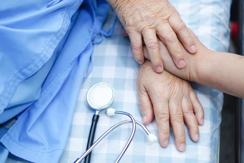 Touching hands Asian senior or elderly old lady woman patient with love, care, helping, encourage and empathy at nursing hospital. Ward : healthy strong medical stock photo