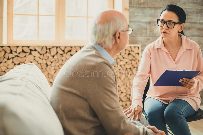 Adult executive woman with severe facial expression. Touching her patient. Adult executive women with severe facial expression touching her ward with calming royalty free stock images