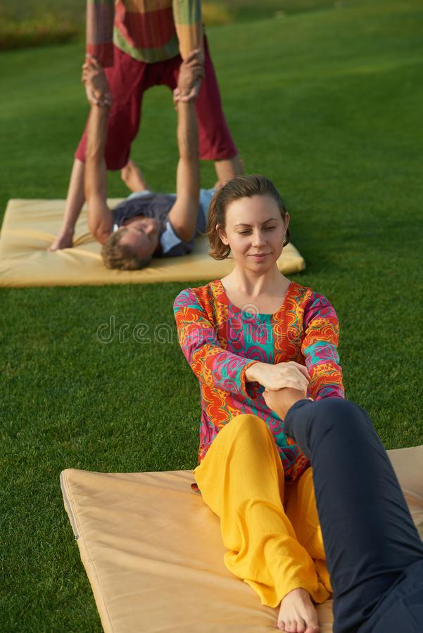 Touching massaging leg, yoga practise. People doing yoga exercises on the park lawn outdoor stock images