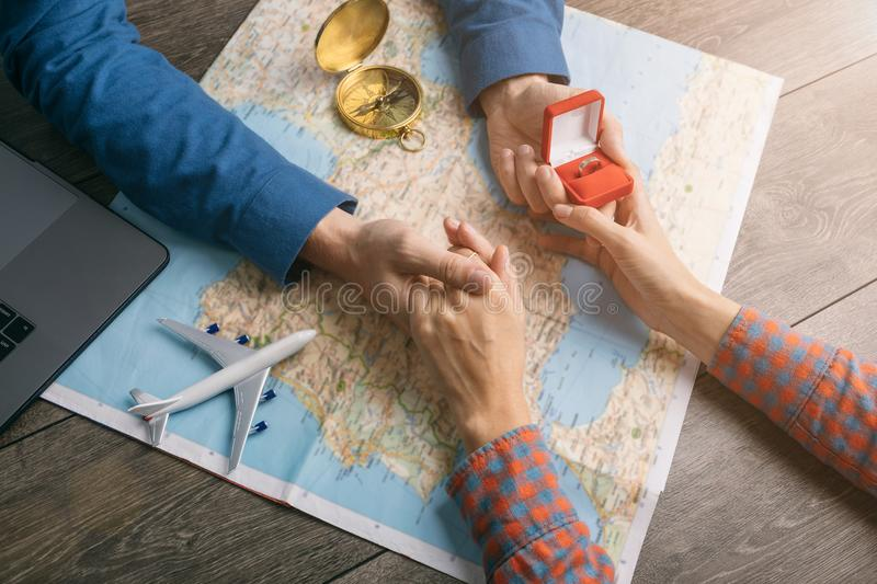 Touching moment the guy proposing at the table with the map and Ring in the box. Travel adicted young couple. Let`s descover world together stock images