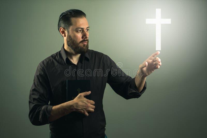 Touchink d'homme de handome de barbe une croix apparaissant dans le ciel images libres de droits