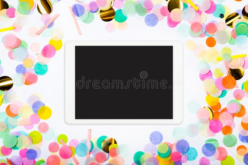 Touchpad with blank screen on colorful confetti background. Color party background with touchscreen pc royalty free stock image