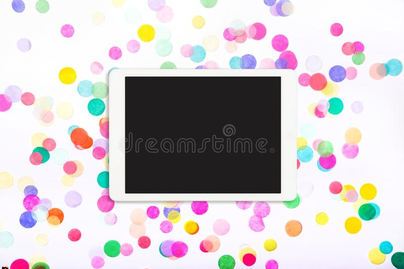Touchpad with blank screen on colorful confetti background stock photo