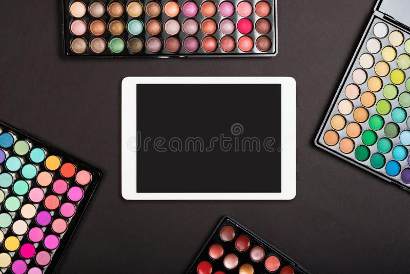 Touchpad met het lege scherm met kleurrijke oogschaduwpaletten op zwarte achtergrond Vlak leg stock foto