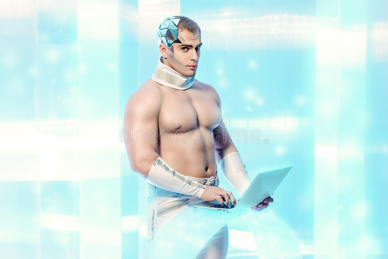 Touchscreen. Handsome muscular man of the future wearing futuristic glasses working on a laptop. Technologies of the future stock photo