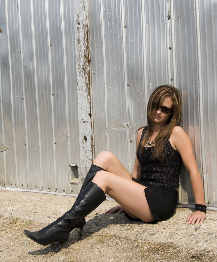 Tough chick. Provocatively dressed woman sitting on ground royalty free stock images