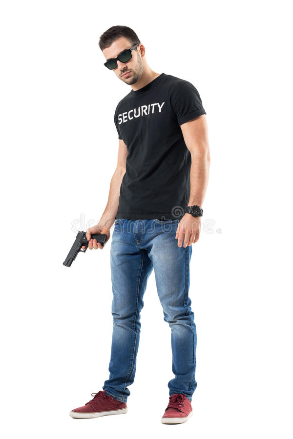 Tough confident plain clothes officer with sunglasses holding gun looking at camera royalty free stock images