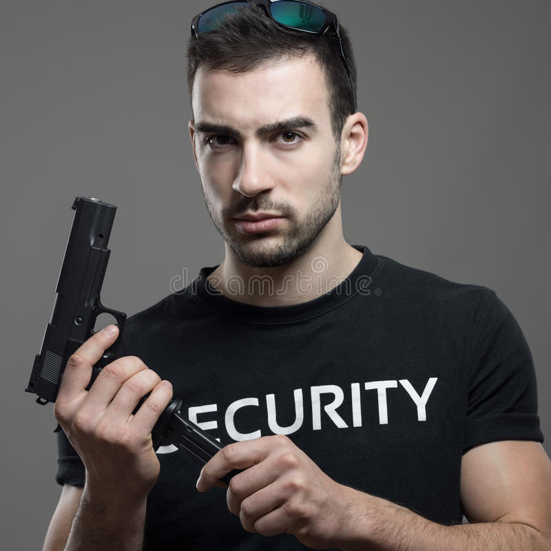 Tough dangerous security officer reloading handgun cartridge threatening look at camera. Atmospheric contrasty portrait over gray studio background stock photos