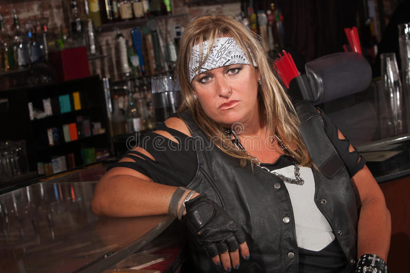 Tough Female Gang Member. Frowning female motorcycle gang member sitting in bar royalty free stock images
