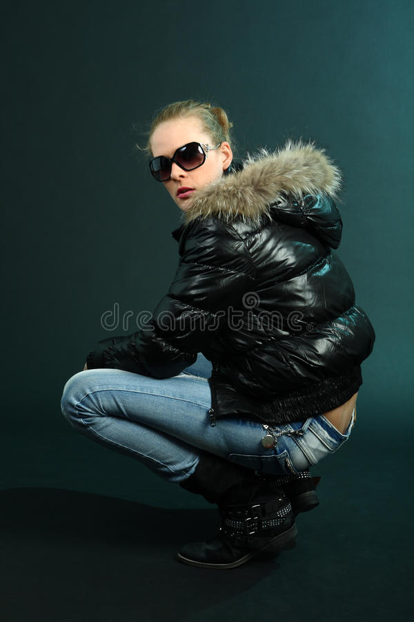 Tough girl in black jacket crouching on dark cyan royalty free stock photography