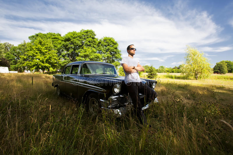Tough Guy with his Vintage Car. A guy looking off into the distance leanin , against his vintage car in field stock image