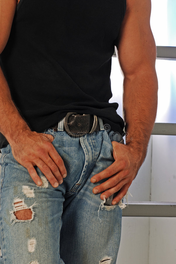 Tough guy torso. Male model with ripped jeans and an old buckle belt posed with hands in pockets stock image