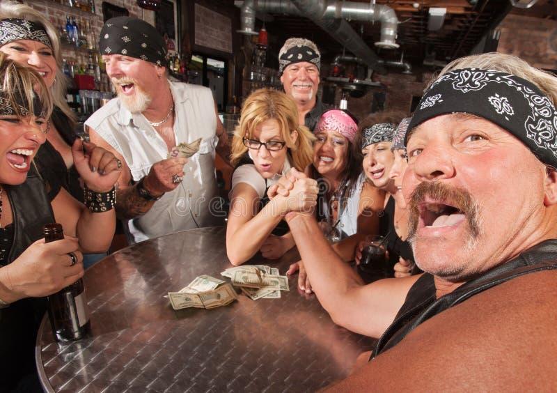 Tough Man Arm Wrestling Nerd. Tough men reacting in arm wrestling match with female nerd stock image