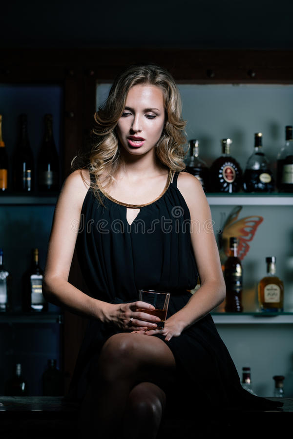 Tough night. Sad woman sitting on the bar counter with glass of whiskey stock photography