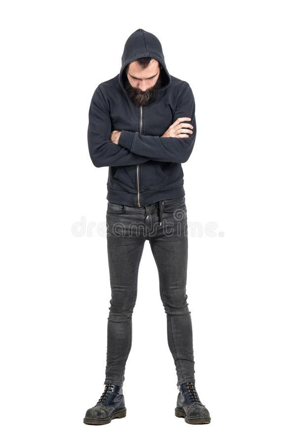 Tough punker in black hooded sweatshirt with crossed arms looking down. Full body length portrait isolated over white studio background stock photos