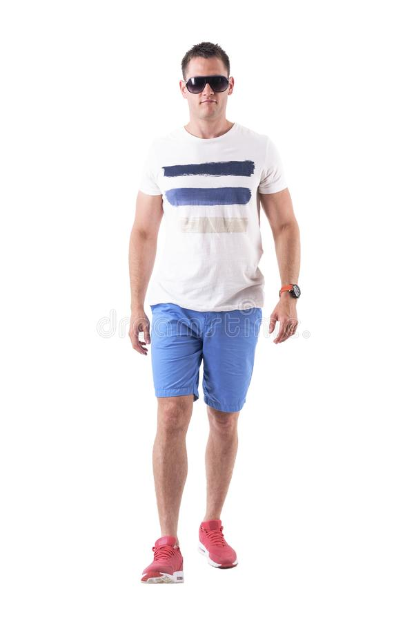 Tough serious man walking towards camera in summer leisurewear. Full body isolated on white background royalty free stock images