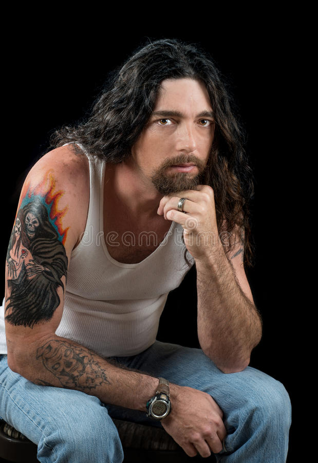 Tough man with long dark hair and beautiful brown eyes stock images