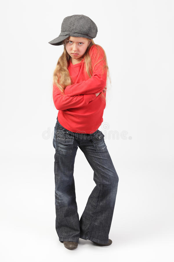Tough suburban kid. Cute suburban blond girl with fashion cap standing with a tough, mad and challenging expression on her face royalty free stock images